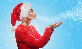 一可爱的年轻女人戴在她的头的一个红色圣诞老人项目帽子,并且在一个红色假日毛线衣吹雪花和闪闪发光 库存照片