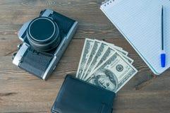 一台减速火箭的照相机、一个钱包有金钱的和一个笔记本有一支笔的在一张木桌上 免版税库存图片