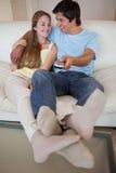 一台可爱的夫妇注意的电视的纵向 库存照片
