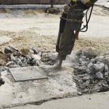 一台固体锤子和水力破碎机沥青、滑行操舵、反向铲装载者和挖掘机的 建筑的a机器 免版税图库摄影