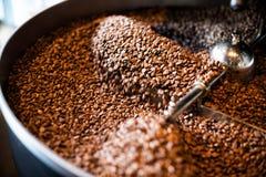 从一台大烘烤器的新近地烤咖啡豆在冷却的圆筒 在豆的行动迷离 免版税库存图片