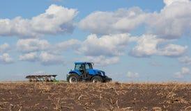 一台大蓝色拖拉机,犁领域反对美丽的天空 免版税库存图片