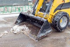一台小黄色推土机清除从雪的街道 免版税库存图片