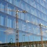 一台建筑用起重机的反射在玻璃门面的 免版税库存图片