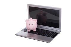 一台开放膝上型计算机的桃红色存钱罐 库存图片