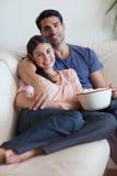 一台微笑的夫妇注意的电视的纵向 免版税库存图片