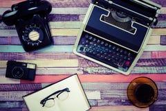 一台打字机和一个减速火箭的电话在一张五颜六色的木桌上 图库摄影