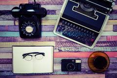 一台打字机和一个减速火箭的电话在一张五颜六色的木桌上 免版税图库摄影