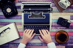 一台打字机和一个减速火箭的电话在一张五颜六色的木桌上 免版税库存照片