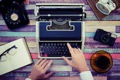 一台打字机和一个减速火箭的电话在一张五颜六色的木桌上 库存图片