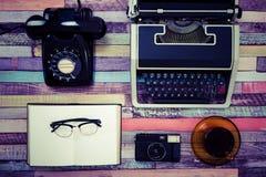 一台打字机和一个减速火箭的电话在一张五颜六色的木桌上 免版税库存图片