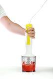 一台搅拌器用在明亮的背景的莓果 进入新鲜的草莓的人` s手果酱 有机夏天饮料 图库摄影