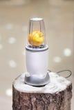 一台搅拌器的接近的看法用在一本多雪的日志的一个苹果 库存图片