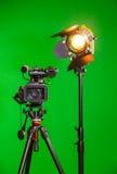 一台摄象机和一盏聚光灯与一个菲涅耳透镜在绿色背景 在内部的摄制 色度钥匙 库存照片
