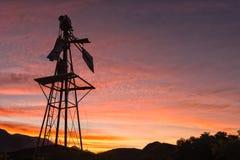 一台残破的风车的剪影反对日落的 库存图片