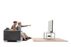 一台沙发和观看的电视的两个成熟人有一个的  免版税库存照片