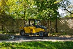 一台沥青夯捣式压路机在一个公园运转在一个晴朗的春日 柏油路修理  库存图片