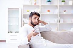 一台浴巾观看的电视的年轻人在家在沙发co 库存图片