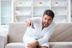一台浴巾观看的电视的年轻人在家在沙发co 库存照片