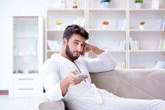 一台浴巾观看的电视的年轻人在家在沙发co 免版税库存照片