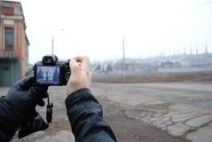 一台照相机在摄影师的手上拍从在远处的照片 免版税库存图片