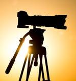 一台照相机的剪影在一个三脚架的在日落 免版税库存图片