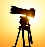 一台照相机的剪影在一个三脚架的在日落 库存照片