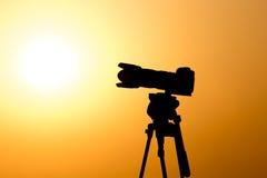 一台照相机的剪影在一个三脚架的在日落 库存图片
