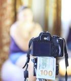 一台照相机,在它下100美元,在焦点 在背景中女孩不聚焦 收入的概念在照片的 免版税库存图片