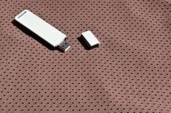 一台现代便携式USB Wi-Fi适配器在棕色运动服被安置由聚酯尼龙fibe制成 免版税库存图片