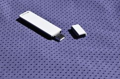 一台现代便携式USB Wi-Fi适配器在紫罗兰色运动服被安置由聚酯尼龙fibe制成 免版税库存照片