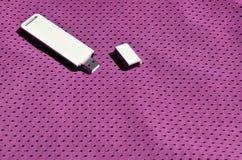 一台现代便携式USB Wi-Fi适配器在紫色运动服被安置由聚酯尼龙fibe制成 免版税库存图片