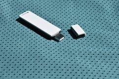 一台现代便携式USB Wi-Fi适配器在蓝色运动服被安置由聚酯尼龙fibe制成 免版税库存照片