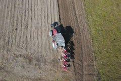 一台红色拖拉机的一位农夫有播种机的在一个私有领域的被犁的土地播种五谷在村庄区域 春天的机械化 免版税库存图片