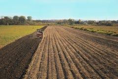 一台红色拖拉机的一位农夫有播种机的在一个私有领域的被犁的土地播种五谷在村庄区域 春天的机械化 图库摄影
