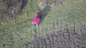 一台红色拖拉机的一位农夫有播种机的在一个私有领域的被犁的土地播种五谷在村庄区域 春天的机械化 影视素材