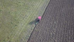 一台红色拖拉机的一位农夫有播种机的在一个私有领域的被犁的土地播种五谷在村庄区域 春天的机械化 股票录像