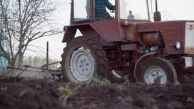 一台红色拖拉机的一位农夫犁他的小剧情的土地 种田的工作 股票录像