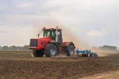 一台红色拖拉机的彩色照片反对蓝天的 免版税图库摄影