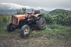 一台老拖拉机停放了在山的路旁在镭以后 图库摄影
