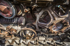一台老拖拉机的生锈和肮脏的轨道和大齿轮在Scrapyard的 免版税图库摄影