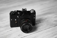 一台老葡萄酒黑色照相机,一台光学仪器为记录或夺取图象在被弄脏的木背景 免版税库存照片