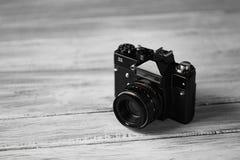 一台老葡萄酒黑色照相机,一台光学仪器为记录或夺取图象在被弄脏的木背景 库存照片