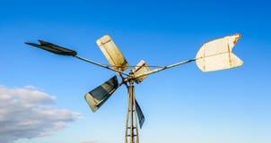 一台老金属开拓地风车的后侧方 免版税图库摄影