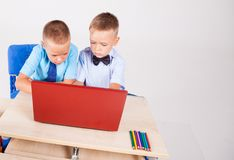 一台计算机的男孩在互联网学校教训 库存照片