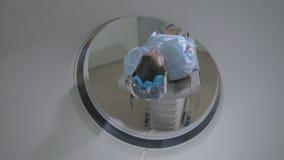 一台紧急医院MRI扫描器的患者 人在磁反应图象设备放置,做地貌的扫描 股票视频