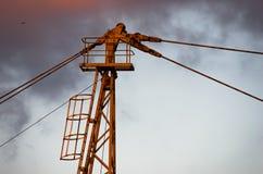 一台黄色建筑用起重机的细节反对多云天空的在日落在贝尔格莱德 免版税库存图片