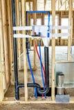 一台洗衣机和烘干机的水管在新建工程 图库摄影