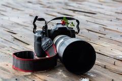 一台dslr照相机的特写镜头与一个大白色透镜和红色莓果的 图库摄影