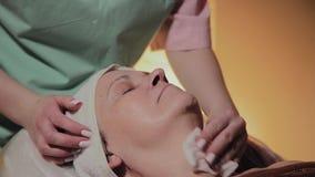 一名专业美容师一名年长妇女的面孔为做法做准备 Cosmetological创新 影视素材